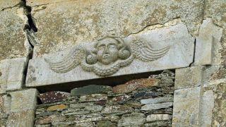 Figura en un dintel de piedra de un caserón de Abres