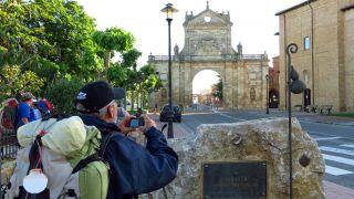 Grupos de peregrinos fotografían el Arco de San Benito, Sahagún