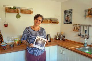 La brasileña Patrícia en la cocina de su albergue con su libro, Só por Hoje